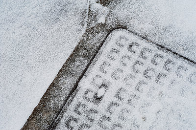 Drain covering lightly covered in snow - p1047m1539872 by Sally Mundy