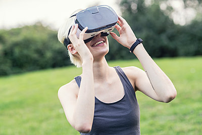Smiling young woman using Virtual Reality Glasses outdoors - p300m1205689 by A. Tamboly