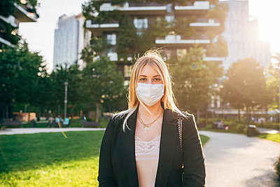 Businesswoman wearing mask standing on footpath in city during sunny day - p300m2202907 by Eugenio Marongiu