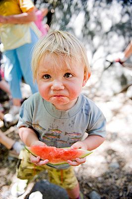A young boy  frowns with his slice of watermelon. - p343m964259 by Kevin Steele