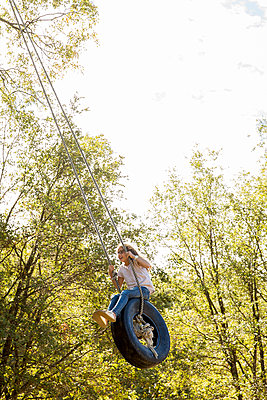 Girl has fun in a tire swing - p756m2125045 by Bénédicte Lassalle