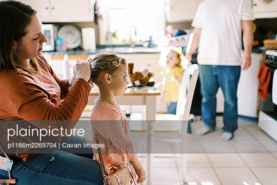 Little preschool age girl getting hair done by her mother in kitchen - p1166m2269704 by Cavan Images