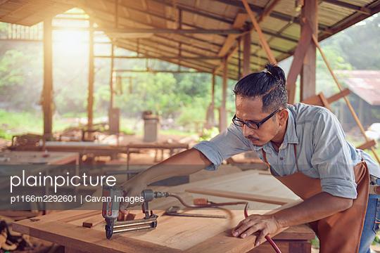 Closeup of a man carpenter using a nail gun.Carpenter using air  - p1166m2292601 by Cavan Images