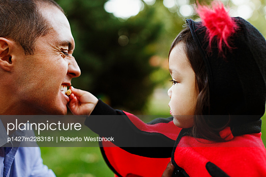 Girl dressed as ladybird feeding father - p1427m2283181 by Roberto Westbrook