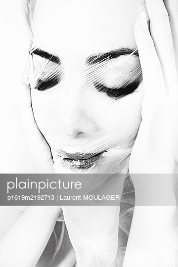 Portrait of a young woman covering her face with plastic wrap - p1619m2192713 by Laurent MOULAGER