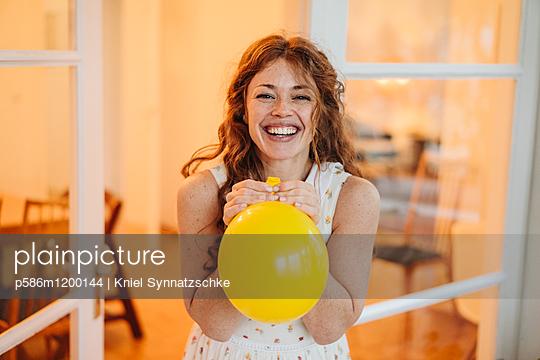 Junge Frau mit einem gelben Luftballon - p586m1200144 von Kniel Synnatzschke