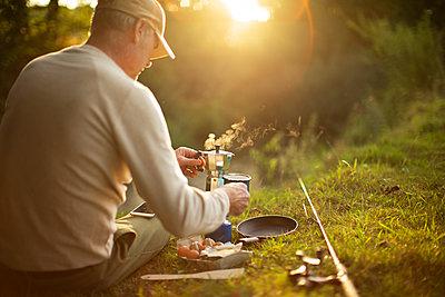 Man taking break from fly fishing pole making coffee on riverbank - p1023m2262030 by Martin Barraud