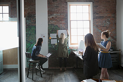Architects meeting, hanging blueprints on brick wall in loft office - p1192m1447465 by Hero Images