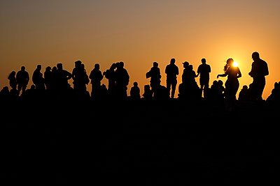Portugal, Algarve, Silhouettes of people relaxing against setting sun at Cape Saint Vincent - p300m2144519 by Michael Reusse (alt)