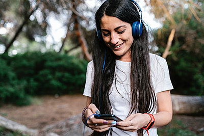 Woman with headset using smartphone in the woods - p300m2202567 by Ezequiel Giménez