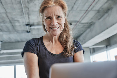 Smiling mature woman with laptop in loft apartment at home - p300m2265213 by Jo Kirchherr