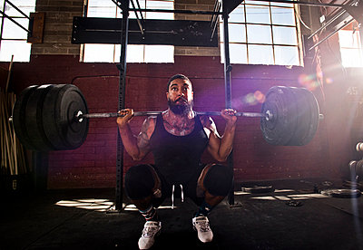 A Crossfit athlete performs a squat.  - p343m1018433 by Rob Hammer