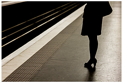 Wartende Frau an der Bahnsteigkante - p567m1212523 von Alexis Bastin