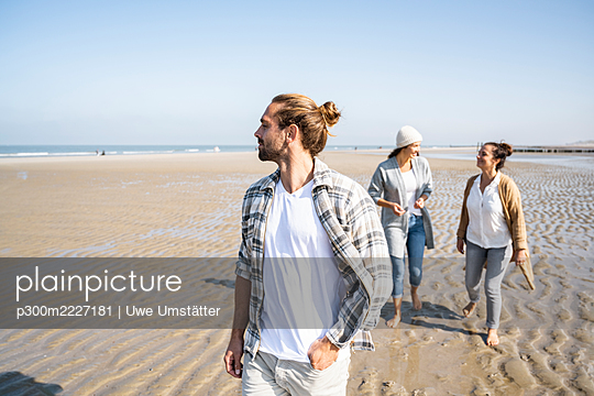 Man looking away while walking with women talking in background at beach - p300m2227181 by Uwe Umstätter