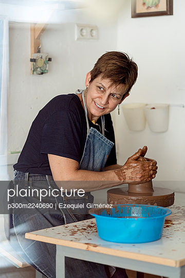 Smiling female potter molding clay while looking away at ceramic workshop - p300m2240690 by Ezequiel Giménez