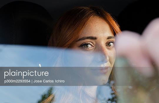 Young redhead woman staring seen through car window - p300m2293554 by Jose Carlos Ichiro