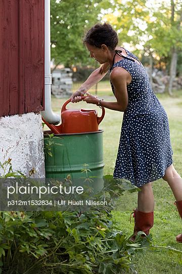 plainpicture   Photo library for authentic images - plainpicture p312m1532834 - Woman filling watering can - plainpicture/Johner/Ulf Huett Nilsson
