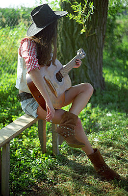 Young woman playing the guitar - p1054m792057 by Maria Kazvan