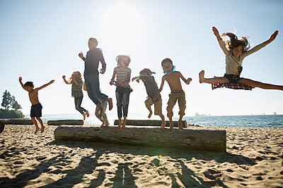 Exuberant boy and girl friends jumping off log on sunny ocean beach - p1192m1511882 by Hero Images