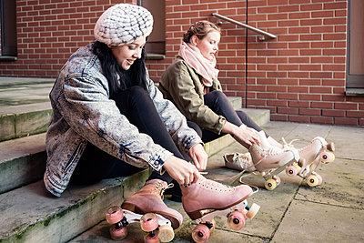 Zwei junge Frauen ziehen Roller Skates an - p1332m1540028 von Tamboly