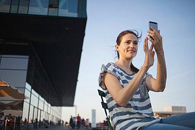 Junge Frau macht ein Foto mit dem Smartphone, Kopenhagen, Dänemark - p586m940587 von Kniel Synnatzschke