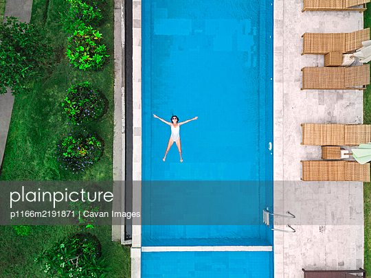 Aerial view of attractive woman floating over water at resort - p1166m2191871 by Cavan Images