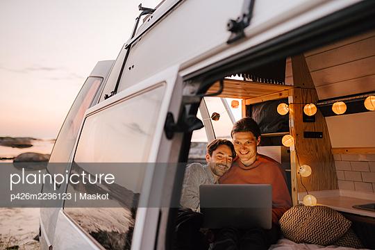 Gay couple using laptop seen through doorway of camping van - p426m2296123 by Maskot