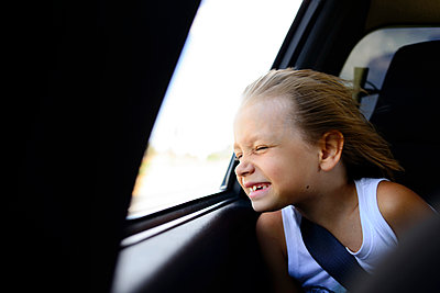 Girl enjoying wind while sitting by window in car - p1166m1486197 by Cavan Images
