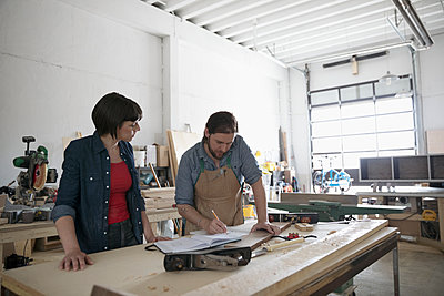 Carpenters sketching plans at workbench in workshop - p1192m1490204 by Hero Images