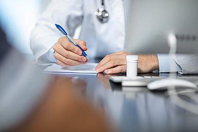 Doctor sitting at his desk taking notes - p300m2004564 von zerocreatives