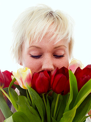 A woman smelling tulips Sweden - p31222330f by Asa Kristensson
