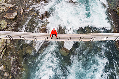 Person standing on footbridge above river - p312m1533117 by Mikael Svensson