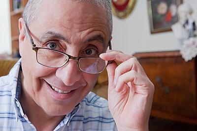 Smiling Hispanic man peering over eyeglasses - p555m1301695 by REB Images