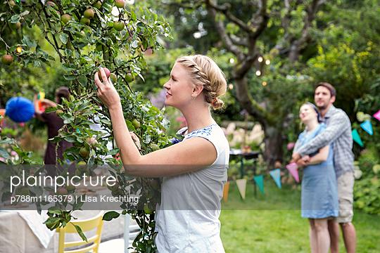 Frau pflückt einen Apfel im Garten - p788m1165379 von Lisa Krechting