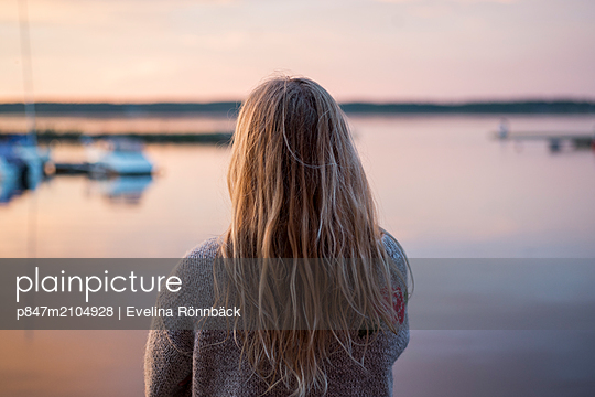 Woman Standing In Front Of Sea During Sunset, Norrbotten, Sweden   - p847m2104928 by Evelina Rönnbäck