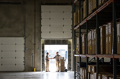 Two warehouse workers shaking hands while standing in the doorway of a loading dock in a large distribution warehouse. - p1100m2002265 by Mint Images