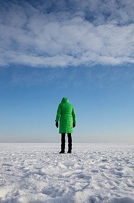 Frau in Grün auf dem Schneefeld - schaut auf dem Boden - p1212m1112931 von harry + lidy