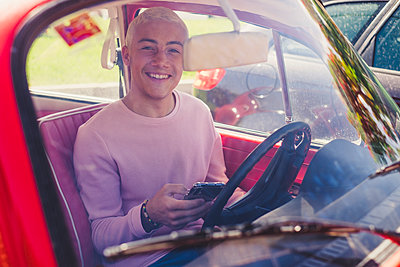 Portrait of smiling teenage boy sitting in vintage car with smartphone looking out of window - p300m2203092 by Simona Pilolla
