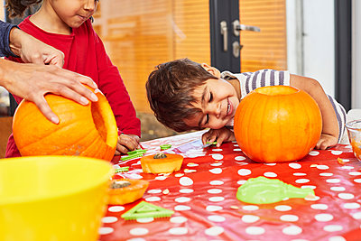 Children carving pumpkin in kitchen - p429m2091667 by Sverre Haugland