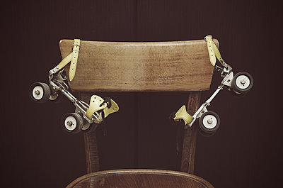 Roller skates hanging on chair - p564m1476817 by Dona