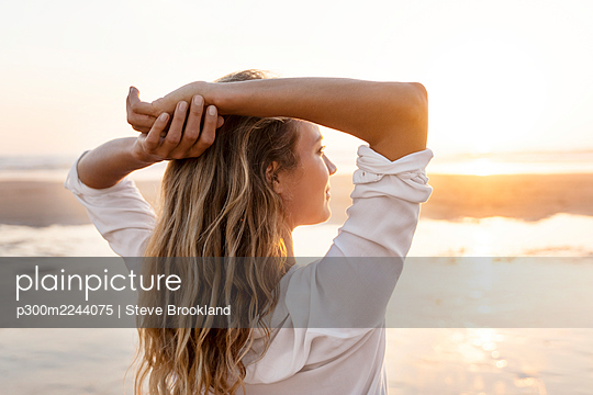 Carefree woman with hands behind head looking at view while standing against sea - p300m2244075 by Steve Brookland