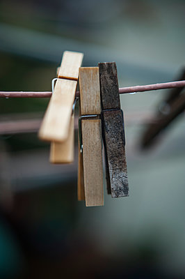 Wooden clothes pegs hanging on a wet washing line - p1047m1061141 by Sally Mundy