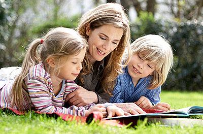 Junge Frau liest Kindern vor - p1237m1050352 von Paul W. Nähr