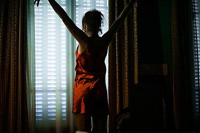 Frau im Dessous mit ausgestreckten Armen am Fenster - p1321m2223434 von Gordon Spooner