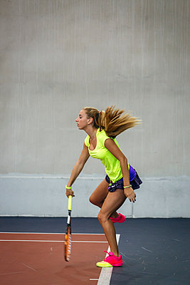 Young woman playing tennis in an indoor tennis center - p300m1059086f by Marco Govel