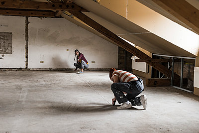Young man and woman measuring floor on construction site - p300m1356147 by Uwe Umstätter