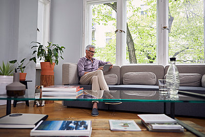 Mature man using tablet on couch at home - p300m2030199 by Rainer Berg