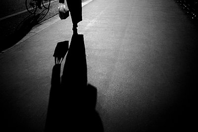 Shadow of person walking on pavement - p388m701641 by McCollum