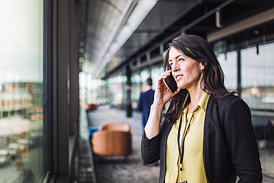 Female entrepreneur talking on smart phone while standing at workplace - p426m2205083 by Maskot