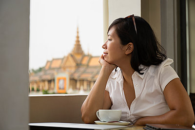 Asian woman looking out cafe window, Phnom Penh, Cambodia - p555m1410020 by Roberto Westbrook